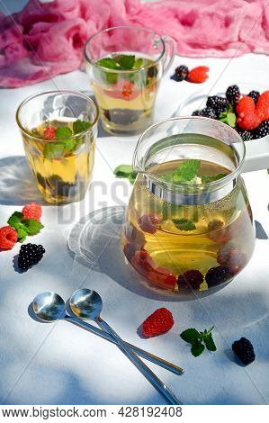 Teapot And Glasses With Refreshing Herbal Tea With Berries On A Light Background With Shadows From O