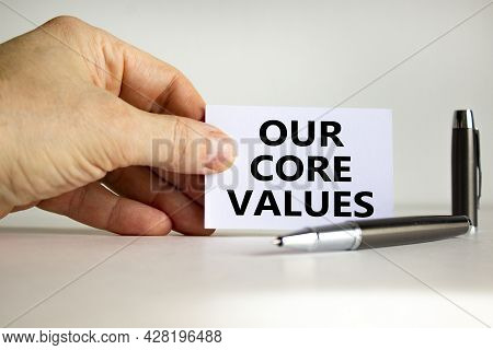 Our Core Values Symbol. White Paper With Words 'our Core Values' In Businessman Hand, Metallic Pen.