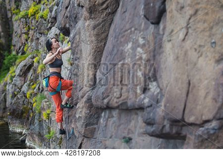 Young Girl Tries Rock Climbing On The Rocks. Girl Climber Climbs A Difficult Route