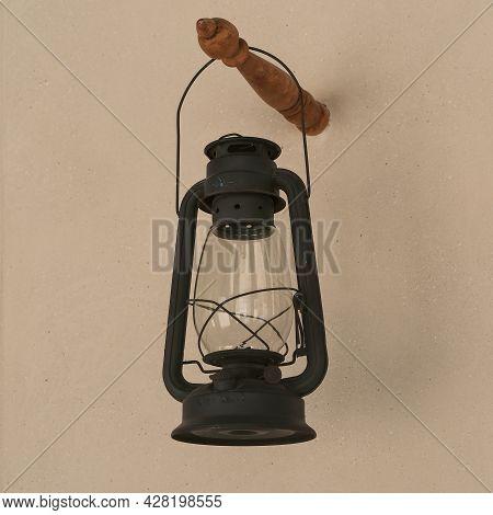 Vintage Black Gasoline Lantern Hanging On Stucco Wall Background After Renovation . Antique Obsolete