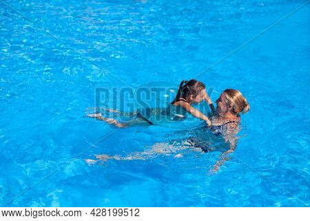 Grandmother And Granddaughter In The Pool. Grandmother And Granddaughter Play Catch-up In The Clear