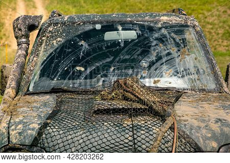 Dirty Car Covered With A Layer Of Swamp Spray From Off-road Travel In Sunny Weather Front View Of Th