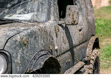 A Muddy Car In A Swamp Layer After An Off-road Trip, A Close-up Of A Side Driver Door With Rear View