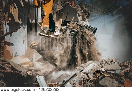 Excavator Bucket Lifts Debris From Demolished House, Sand And Dust Pouring, House Destruction.