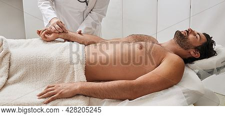 Man Enjoys Body Acupuncture In Chinese Traditional Medicine Wellness Center. Reflexologist Makes Han