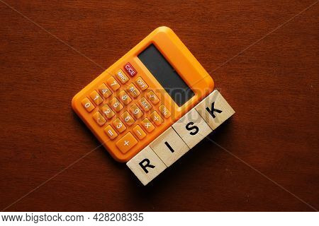 Calculator And Wooden Block With The Word Risk. Calculated Risk Concept. A Risk That You Consider Wo