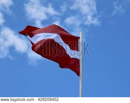 Latvian Flag Waving In Strong Wind On A Sunny Summer Day