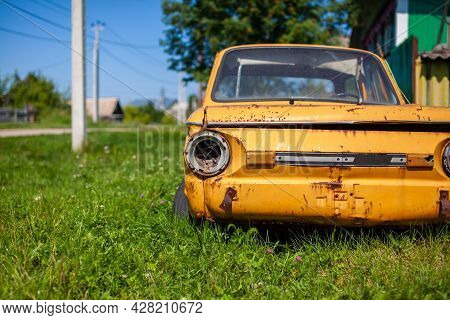 Old Yellow Wrecked Car In Vintage Style. Abandoned Rusty Yellow Car. Closeup Of The Headlights Of Th