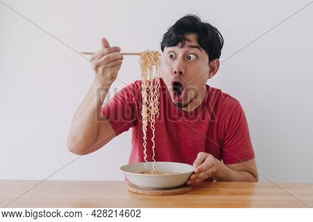Wow And Surprised Funny Face Of Asian Man Eat Instant Noodle.
