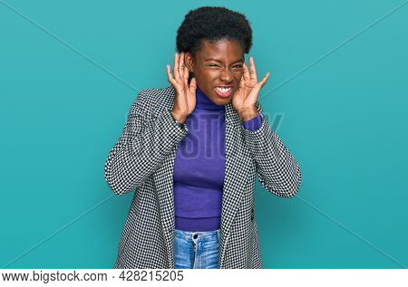 Young african american girl wearing casual clothes trying to hear both hands on ear gesture, curious for gossip. hearing problem, deaf