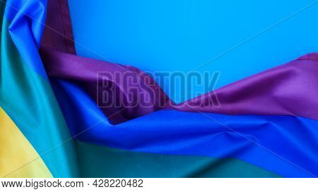 Rainbow Flag On Blue Background With Copy Space. Rainbow Lgbtq Flag Made From Silk Material. Symbol