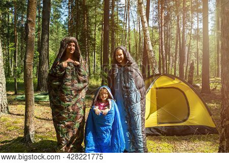 Family Of Tourists From A Father, Mother And Little Daughter Pose In Sleeping Bags Near A Tent. Fami