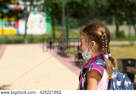 Girl With A Backpack Near The School After Classes With The Medical Mask Removed, Unhappy, Tired. Co
