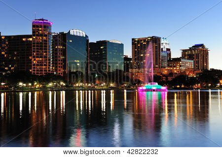 Orlando downtown skyline panorama over Lake Eola at dusk with urban skyscrapers and clear sky.