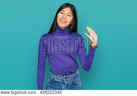 Beautiful young asian woman wearing casual clothes waiving saying hello happy and smiling, friendly welcome gesture