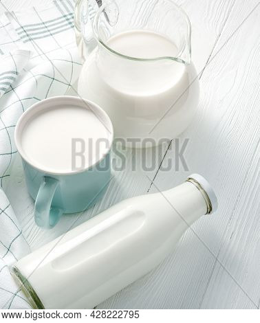 Mug Of Milk And Jug Of Milk And Napkin On White Wooden Table. Top View Flat Lay. Bottle Of Milk On W