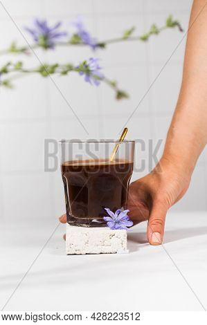 Chicory Drink In A Transparent Mug With Chicory Flowers In The Foreground.