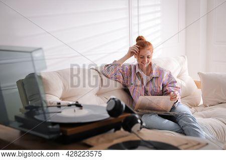 Young Woman Choosing Vinyl Disc To Play Music With Turntable At Home