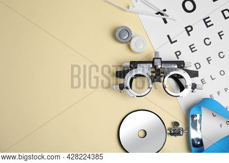 Different Ophthalmologist Tools On Beige Background, Flat Lay. Space For Text