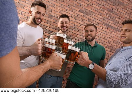 Friends Clinking Glasses Of Beer Near Red Brick Wall