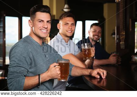 Happy Friends With Tasty Beer In Pub