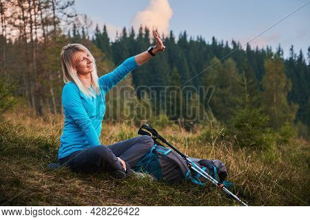 Happy Blonde Woman Sitting On Dry Grass And Covering Her Face With Outstretched Hand From Soft Sunli