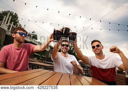 Friends Clinking Glasses Of Beer In Outdoor Cafe