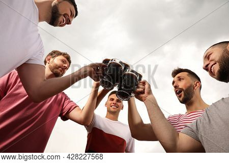 Friends Clinking Glasses With Beer Outdoors, Low Angle View