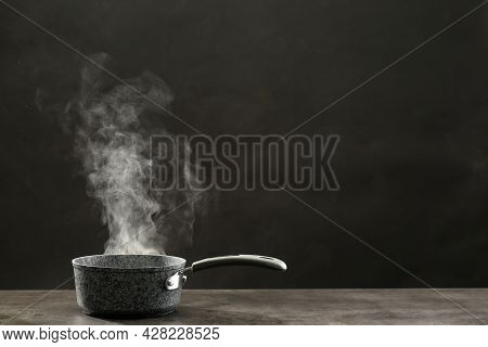 Steaming Saucepan On Grey Table Against Dark Background
