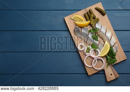 Sliced Salted Herring Fillet Served With Parsley, Pickles, Onion Rings And Lemon On Blue Wooden Tabl