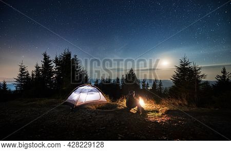 Side View Of Young Man Sitting On Grass Near His Lighted Tent And Watching The Night Stars And Moon