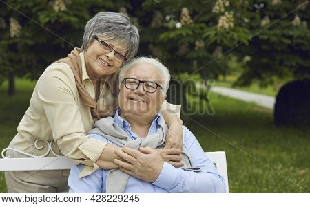 Portrait Of Happy Senior Couple Smiling And Looking At Camera In Green Summer Park