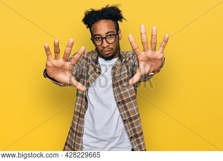 Young african american man with beard wearing casual clothes and glasses doing frame using hands palms and fingers, camera perspective