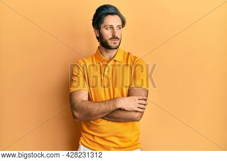 Young hispanic man wearing casual yellow t shirt smiling looking to the side and staring away thinking.