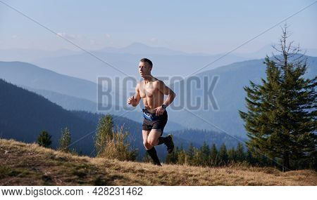 Professional Athlete Trail Runner With Well-developed Muscles Of Torso Running On Mountain Meadow In