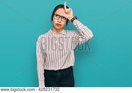 Young hispanic girl wearing casual clothes and glasses making fun of people with fingers on forehead doing loser gesture mocking and insulting.