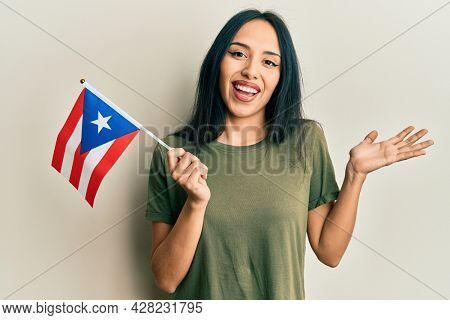 Young hispanic girl holding puerto rico flag celebrating achievement with happy smile and winner expression with raised hand
