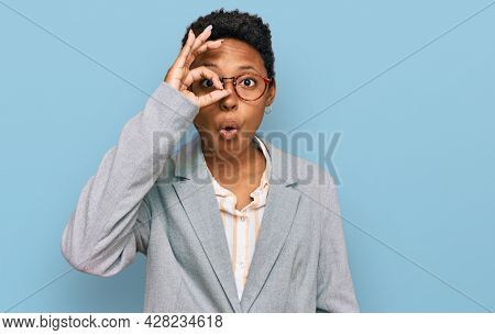 Young african american woman wearing business clothes doing ok gesture shocked with surprised face, eye looking through fingers. unbelieving expression.