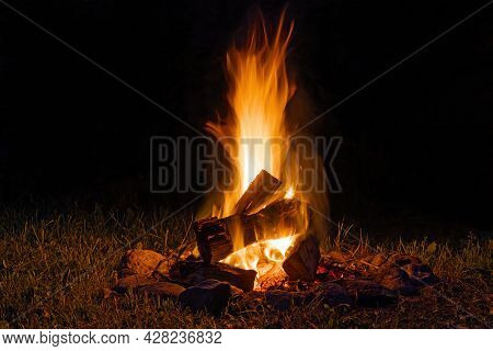 A Colorful Flaming Bonfire With Logs Burning In The Night. Fireplace With Blazing Firewood On The Gr
