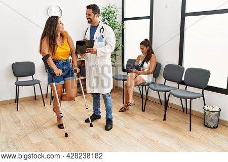 Young hispanic doctor and patient woman looking diagnosis standing at medical clinic waiting room.
