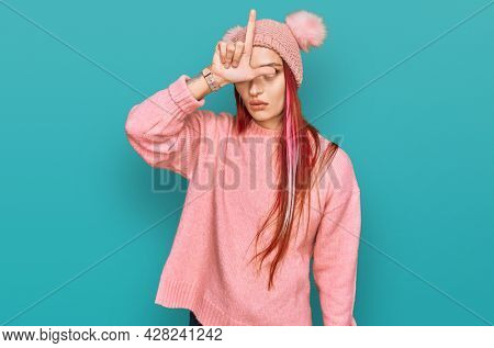 Young caucasian woman wearing casual clothes and wool cap making fun of people with fingers on forehead doing loser gesture mocking and insulting.