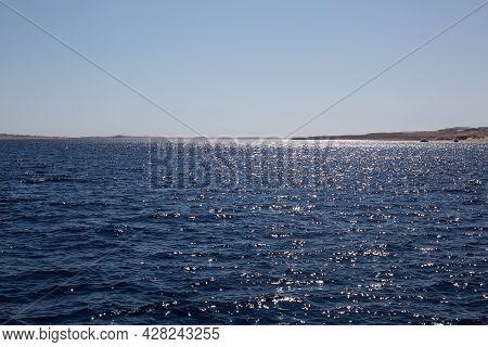 Peaceful Seascape. Beautiful Blue Sky Over Calm Sea With Sunlight Reflection. Sea Waves.