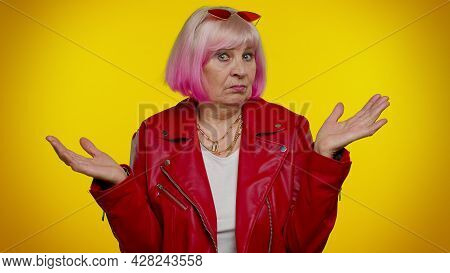 No Idea, I Dont Know Answer. Puzzled Clueless Uncertain Mature Old Granny Woman Raising Hands In Hel