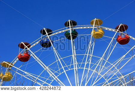 empty attraction wheel on blue sky background in park