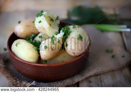 Boiled Young Potatoes With Herbs And Butter In A Bowl.