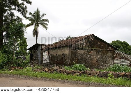 Stock Photo Of Old, Damaged Red Brick House With Pyramid Shape Roof Top In Very Green Landscape Of V