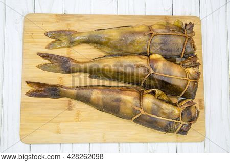 Terpug (latin: Hexagrammos Stelleri) Hot Smoked Without Heads Tied With A Rope On A Wooden Board. Fo
