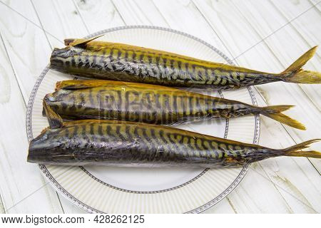 Mackerel (lat. Scomber) Hot Smoked On A Round Plate With A Wooden Table Background. Food Is A Delica