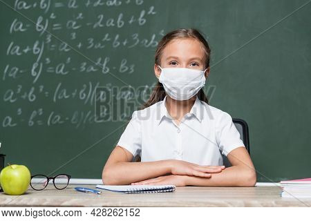 Schoolkid In Medical Mask Sitting At Desk Near Apple, Notebook, Eyeglasses And Blurred Chalkboard