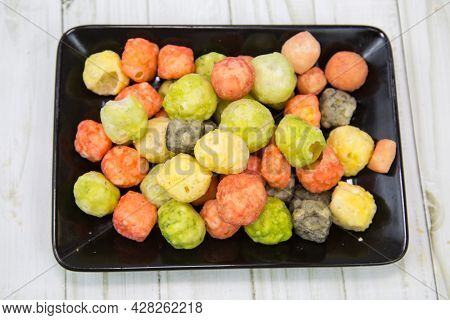 Bright Cheese Balls Mix On A Black Rectangular Plate With A Wooden Table Background. Food Is A Delic